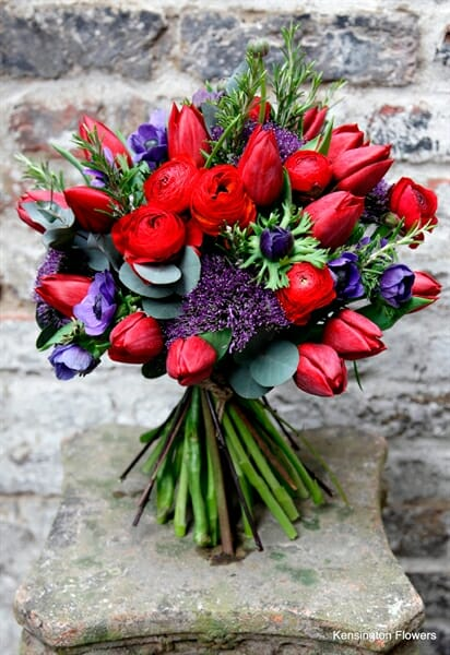 Photo showing a photo of a vivid red and purple Seasonal Hand Tied Bouquet from Kensington flowers