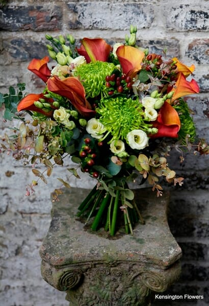 Photo showing a sample of an autumnal Seasonal Hand Tied Bouquet, oranges and greens from Kensington flowers