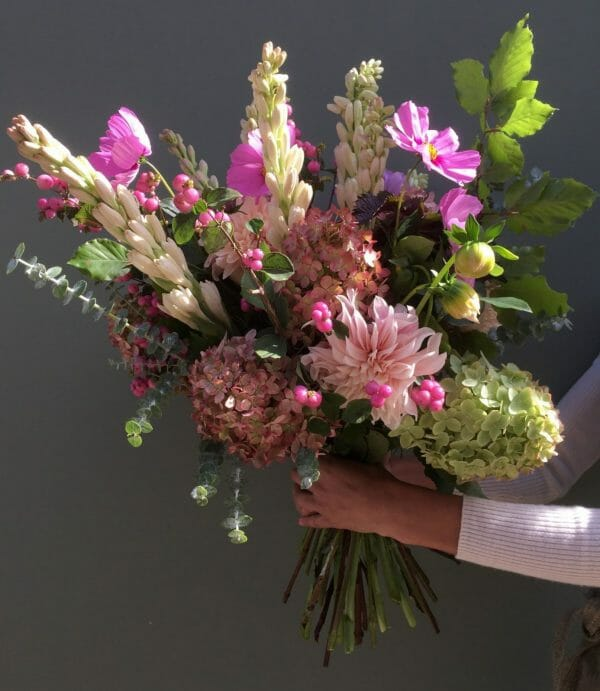 Photo showing a sample of a seasonal hand tied bouquet in dusky pink autumn colours available at Kensington flowers London