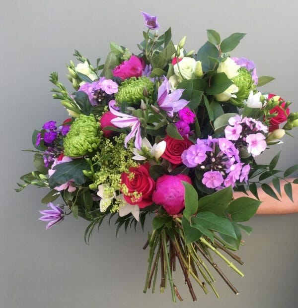 Photo showing a sample of a Seasonal hand tied bouquet vivid and mixed colours Kensington flowers London