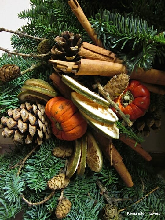 Photo showing a close up of a Christmas door wreath of cones, fruit slices and fresh pine, available from Kensington flowers
