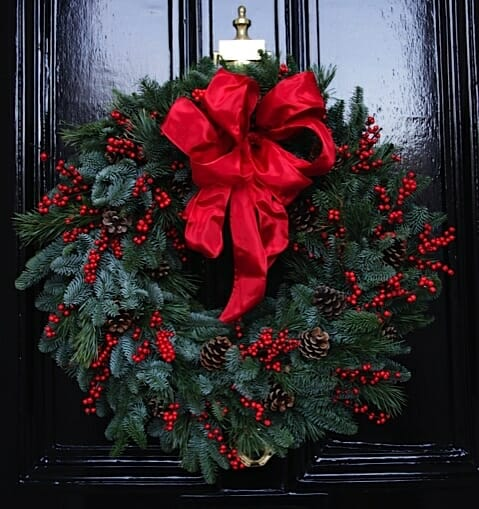 Photo showing a Christmas door wreath of cones, ilex red berry and fresh pine, available from Kensington flowers
