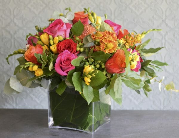 Photo showing a sample image of seasonal vase arrangement mixed vivid colours Kensington flowers