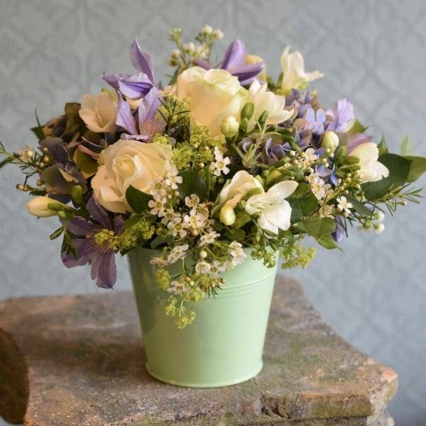 Photo showing a sample image of a bucket of flowers in pastel colours available to order from Kensington flowers, London