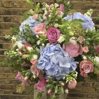 Photo showing a sample of a large florist choice summer bouquet pinks and blues, Kensington flowers