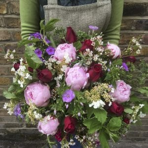 Photo showing a sample of a large florist choice summer bouquet pinks and red,Peonies, scented red roses and phlox from Kensington flowers