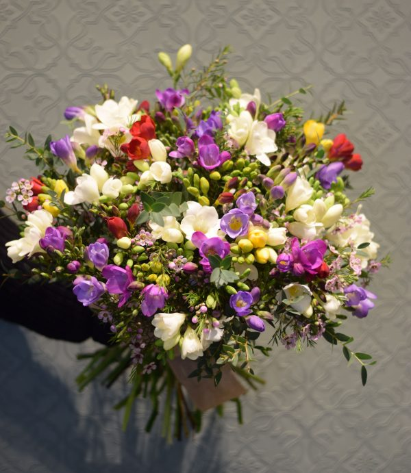 Photo showing a mixed colour freesia scented bouquet en masse Kensington flowers