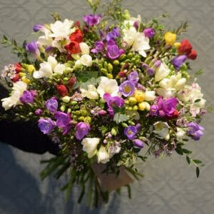 Photo showing a mixed colour freesia scented bouquet en masse Kensington flowers