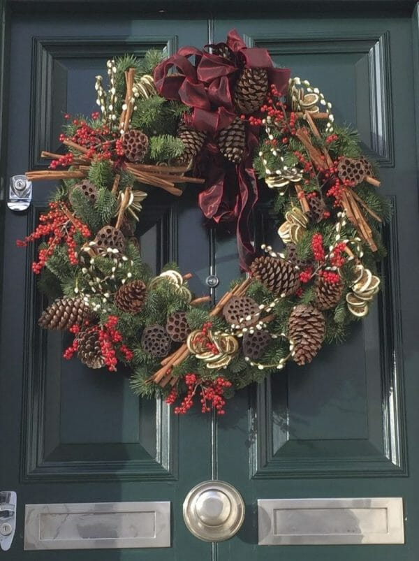 Photo showing a Christmas door wreath of festive fruits, red berry, pussy willow and cinnamon, cones and fresh pine, available from Kensington flowers