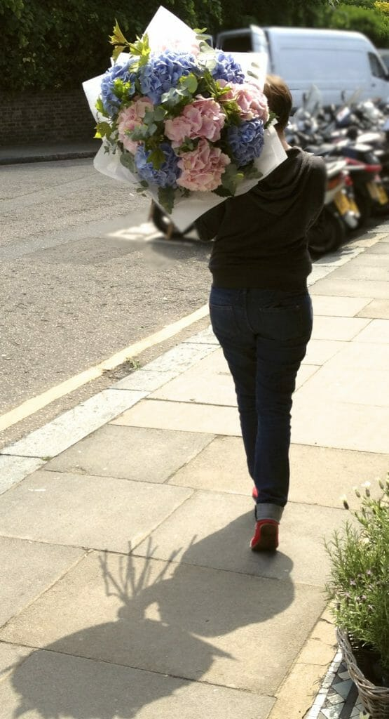 Photo showing a London Flower delivery - florist on foot with large bouquet Kensington flowers
