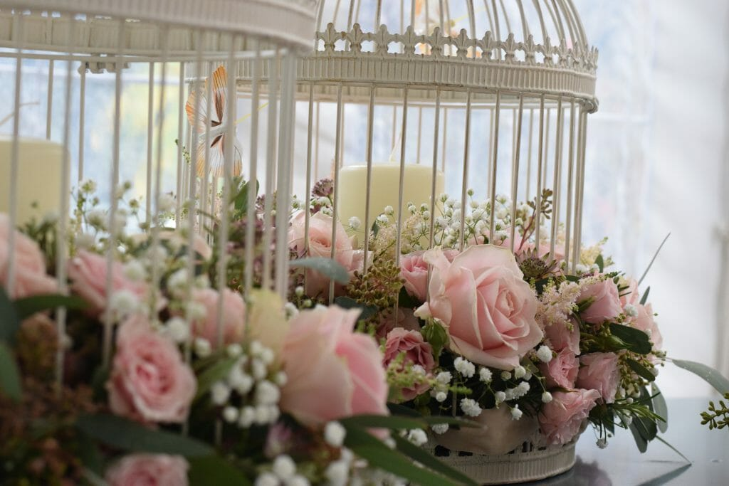 Photo showing a sample of pale pink rose Christening Flower arrangements in birdcages from Kensington flowers