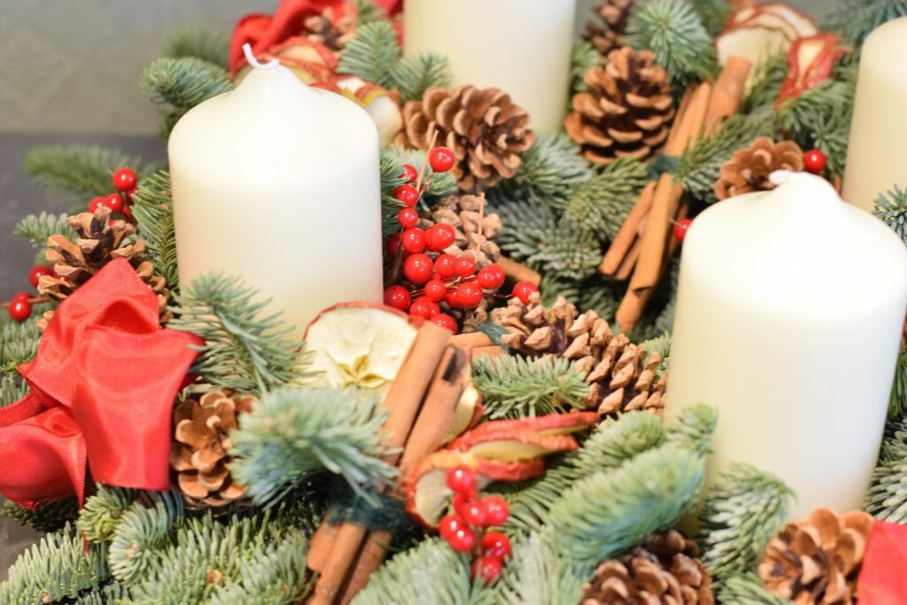 Red advent wreath including fresh pine, apple slices, cinnamon and berry. Kensington flowers
