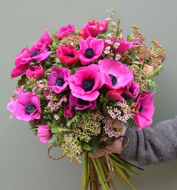 Photo showing a sample of a Pink anemone florist choice spring bouquet from Kensington flowers, London