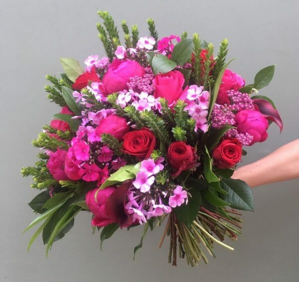 Photograph of a vivid seasonal rose bouquet available from Kensington Flowers London
