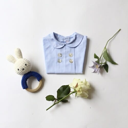 Photo showing a Victoire & Lou gift box, delivered with flowers as a beautiful gift. The Welcome Baby Boy Gift Box Included in the box: Amaia Baby blue shirt with a handmade rattle available at Kensington flowers