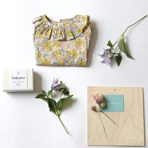 Photo showing a picture of a Victoire & Lou gift box, delivered with flowers as a beautiful gift. The Welcome Baby Girl Gift Box Included in the box: Amaia Baby shirt (6 months) with an Enfance Protective and organic Soothing Soap