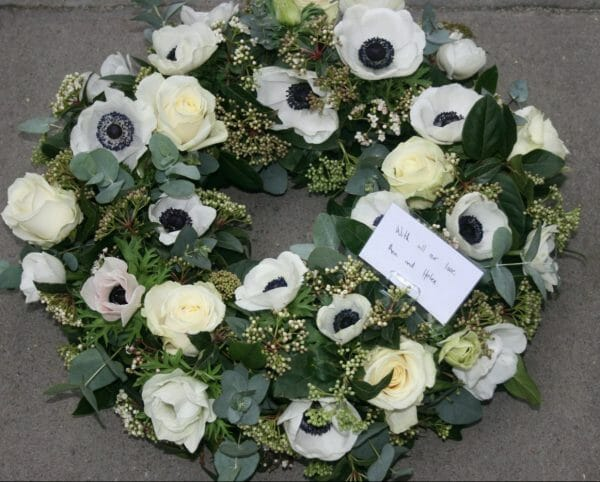 Photo of a White floral wreath funeral tribute of anemones and roses from Kensington flowers