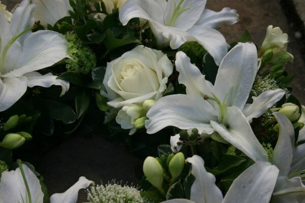 A photo of a close up of an arrangement of Rose and lily funeral flowers