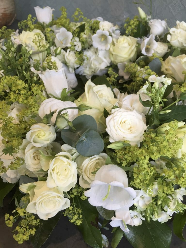 Photo showing a close up image of a white floral arrangement roses Kensington flowers
