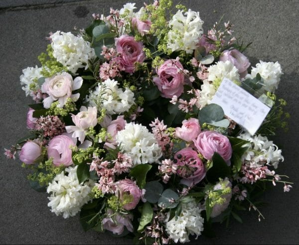 Photo of a pink and white Funeral flowers wreath sympathy tribute