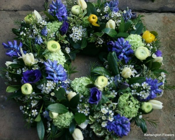 Funeral wreath sympathy tribute blue, lemon and white spring flowers from Kensington flowers