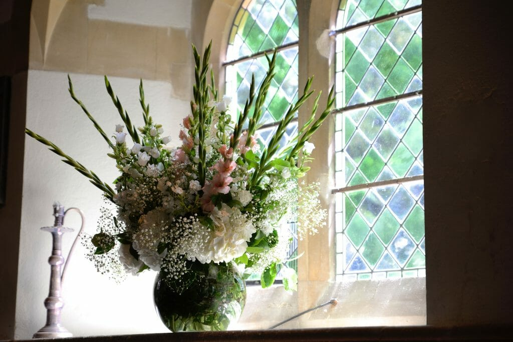 Photo of Church flowers, a vase display of hydrangeas, gyp and gladioli, pastel pink and whites. Kensington flowers