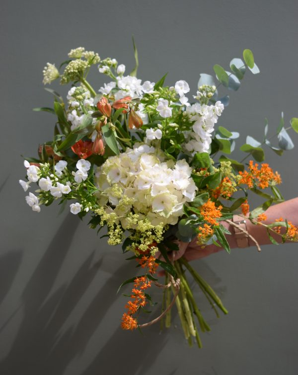 A photo showing a sample bouquet of a Handful flowers bunch florist choice of colours white and orange Kensington flowers