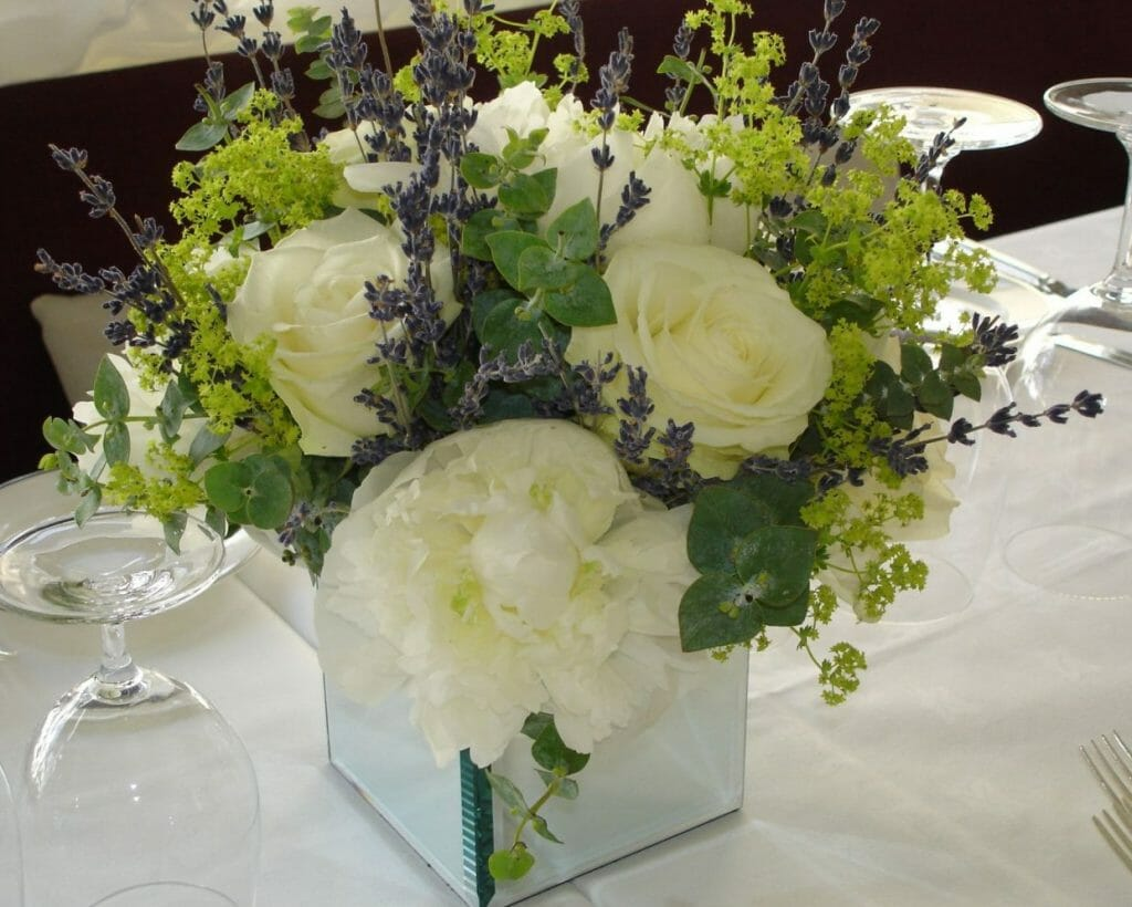 Photo of a mirror cube vase filled with an arrangements of white peonies white roses fresh lavender and alchemila mollis made by Kensington flowers
