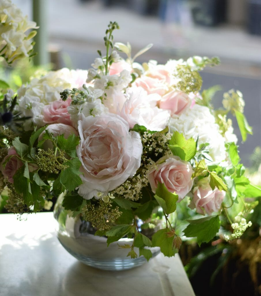 Photo of pale pink Peonies, roses, white hydrangeas and stocks arranged in silver round bowl Kensington flowers
