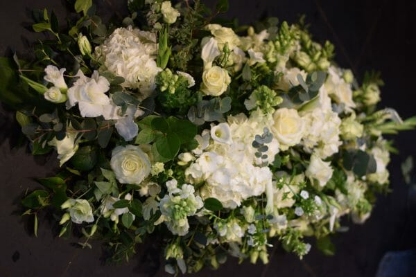 Photo of a funeral spray arrangement of all white flowers funeral flowers from Kensington flowers.