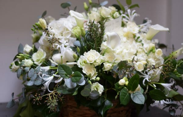 Photo of a posy arrangement of all white flowers funeral flowers from Kensington flowers.