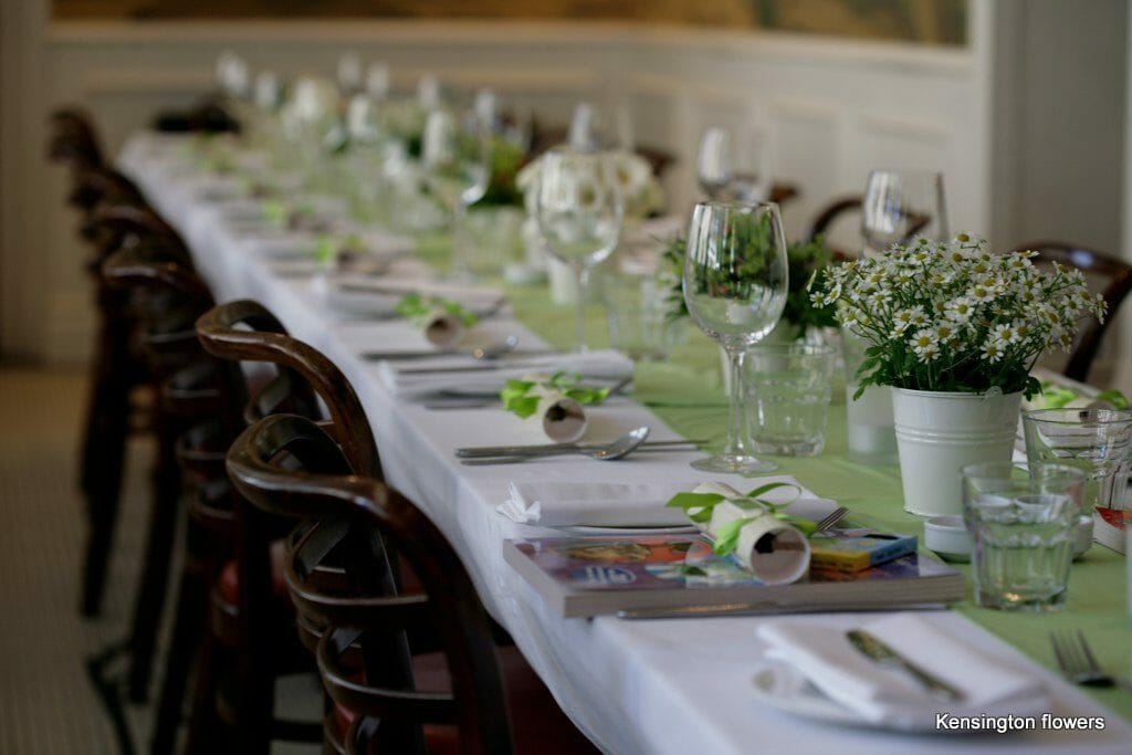 Photo of a long rectangular dining table decorated with with a line of small bucket floral decorations Kensington flowers