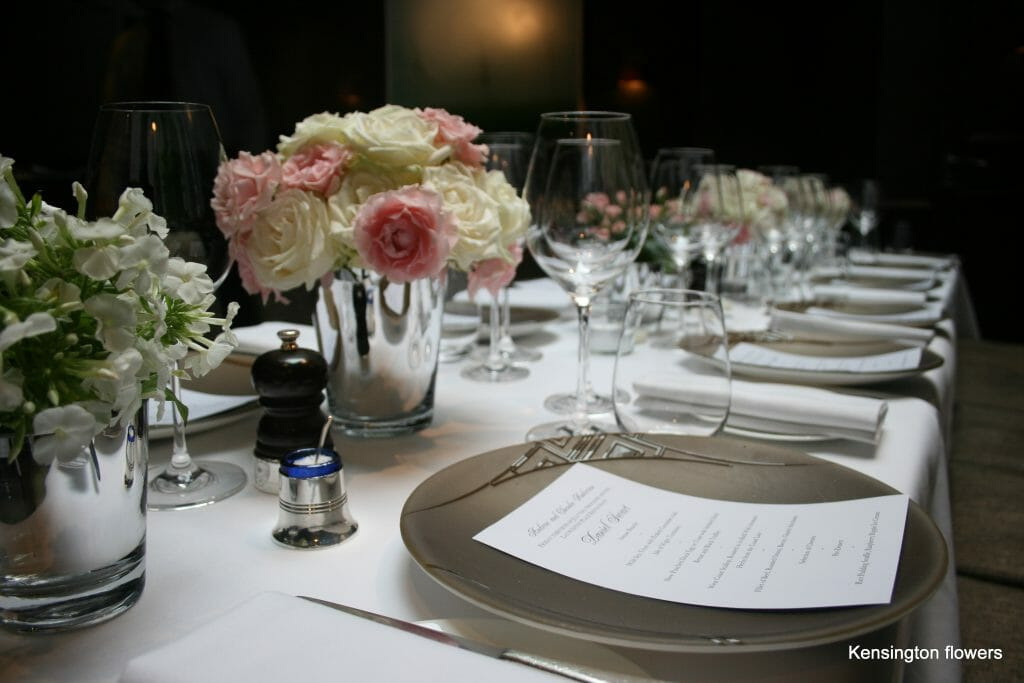 Photo of a line of low silver vase arrangements filled with mix pink and cream flowers for dining table party flowers Kensington Flowers