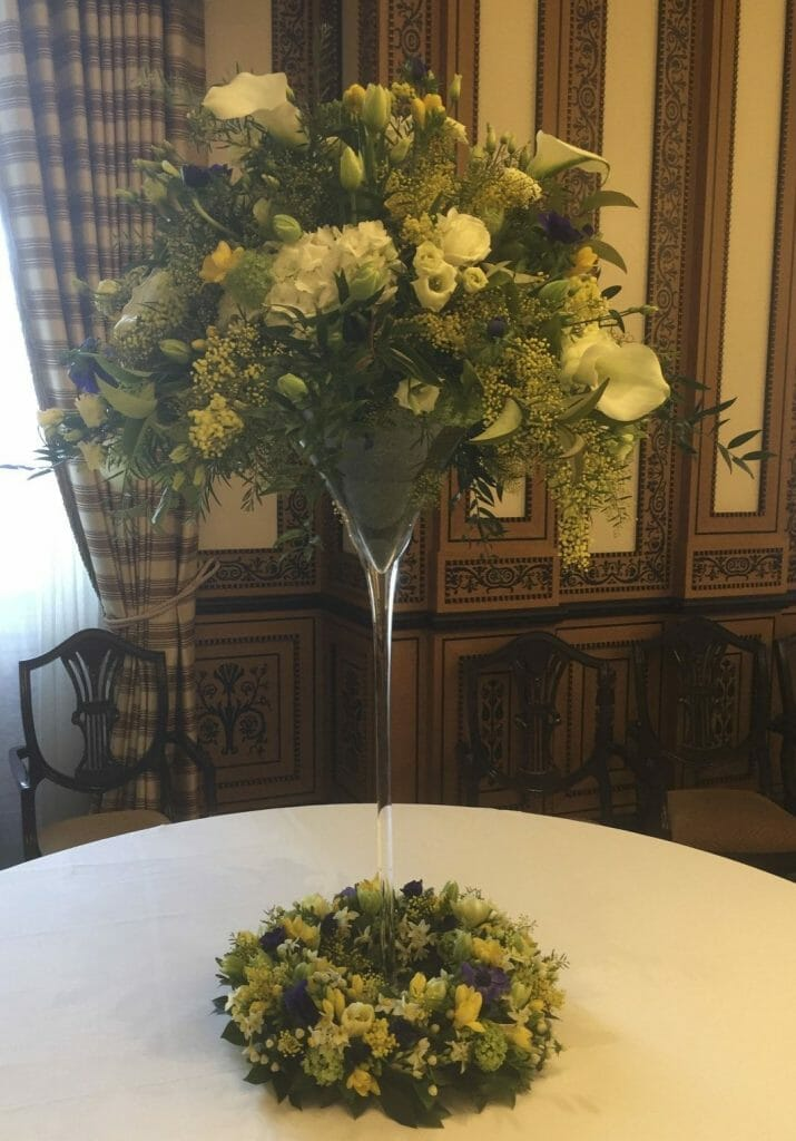 Photo showing a tall Martini vase decorated with yellow, white and blue spring flowers Kensington flowers