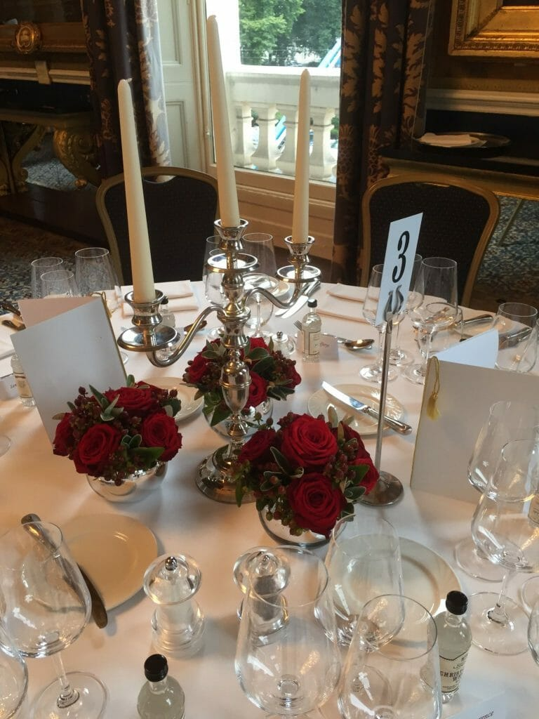 Photo of a dining table dressed with a Trio of small silver bowls filled with red roses and berries, circling a candelabra Kensington Flowers
