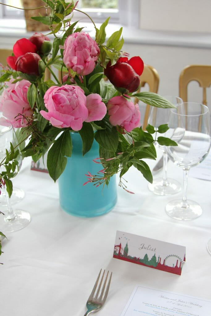 Photo of a wedding table dressed with a turquoise vase filled with pink and red peonies with trailing jasmine