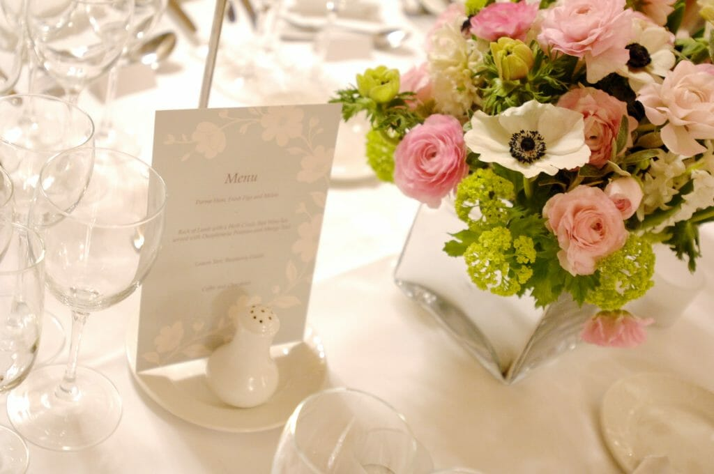 Photo of a low silver cube vase arrangement for dining table party flowers created by Kensington Flowers