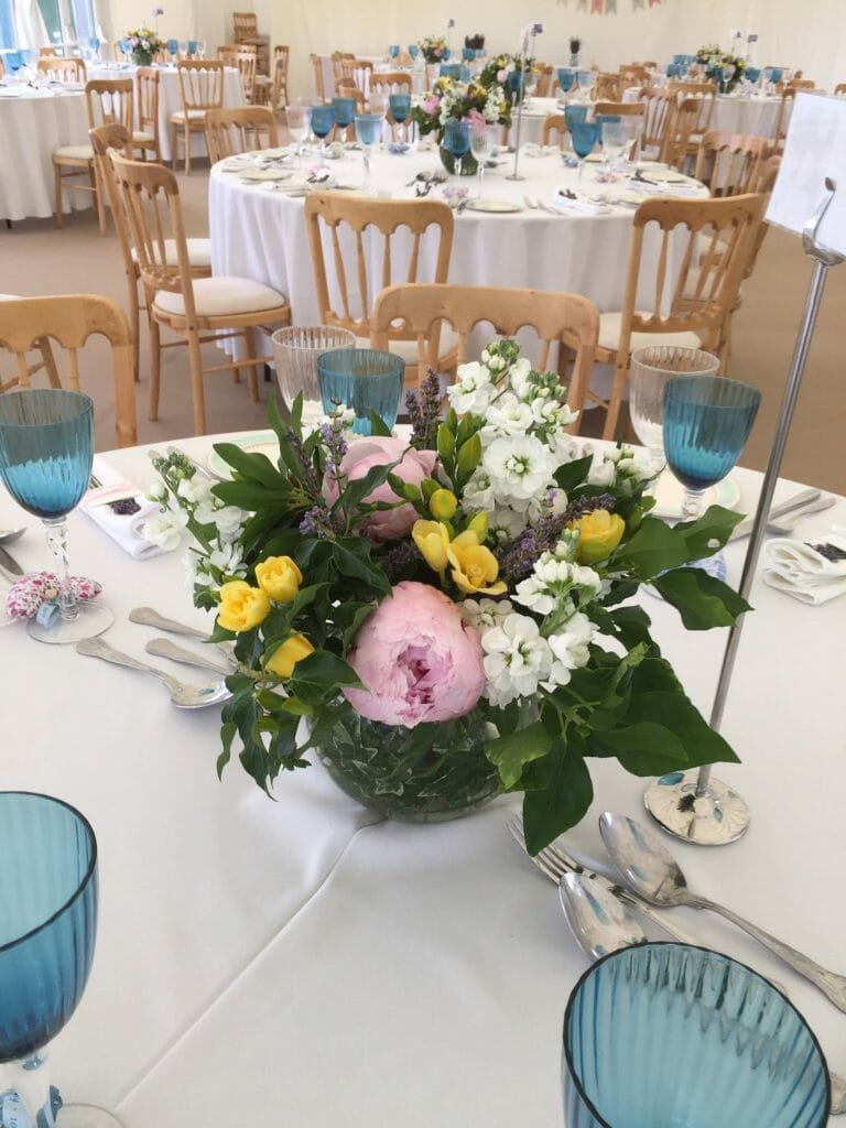 Photo of a marque dressed for a wedding and table arrangements of mix colour summer flowers by Kensington flowers
