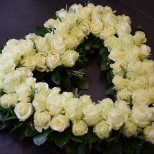 Photo of a funeral tribute, a white rose open heart with foliage collar. White roses arranged en masse