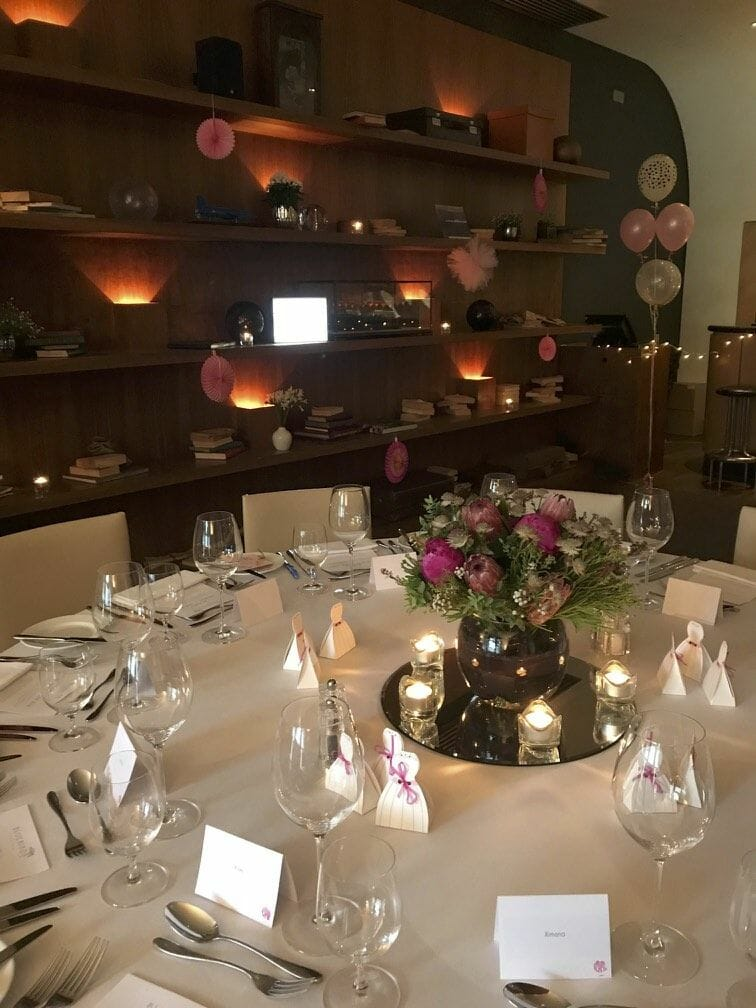 Photo showing a night room setting of a dining table with a pink vase arrangement in a bowl made by Kensington flowers