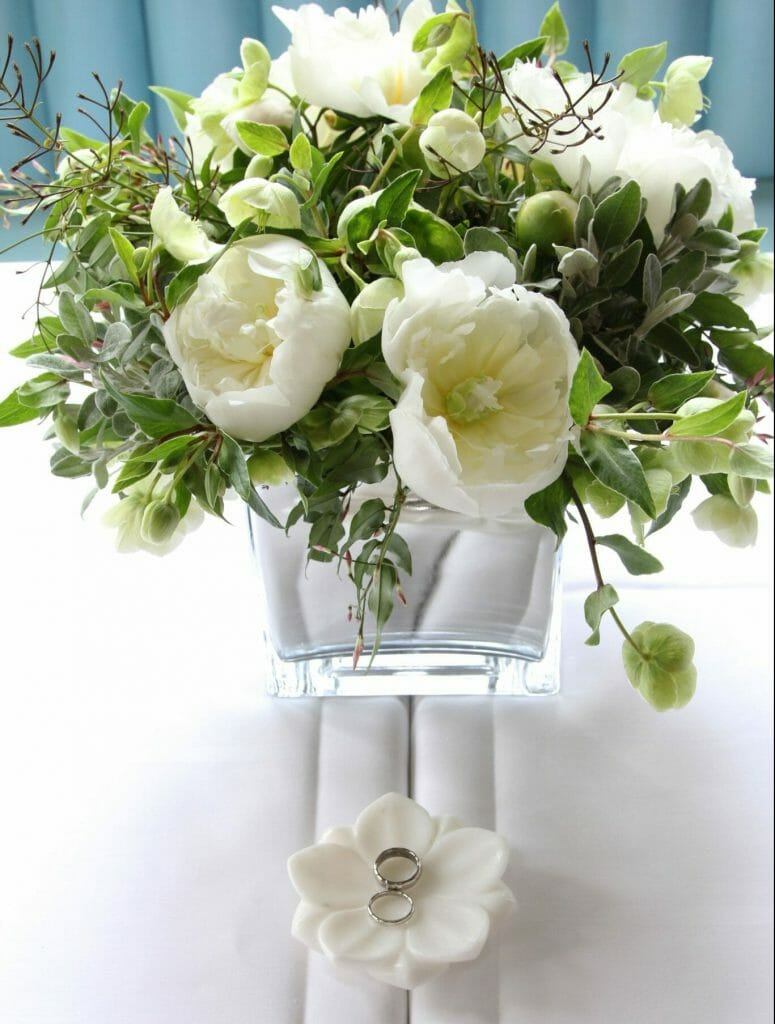 Photo of a registrars table dressed with a mirrored vase of white peonies, hellebores and jasmine Kensington flowers