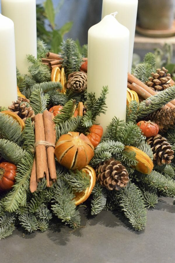 Photo showing a close up of Christmas Advent candle arrangement mixed fruits, cinnamon and cones Kensington Flowers London