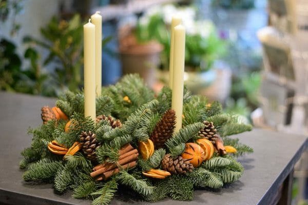 Photo showing a sample of an Christmas Advent wreath of pines, orange fruits cinnamon and cones Kensington Flowers London