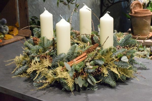 Photo showing a sample of a Christmas Advent wreath, pine, cones, lichen, cinnamon and gold leaf Kensington Flowers London