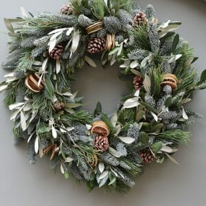 Christmas door wreath of mixed foliages and green fruit available to order from Kensington flowers London