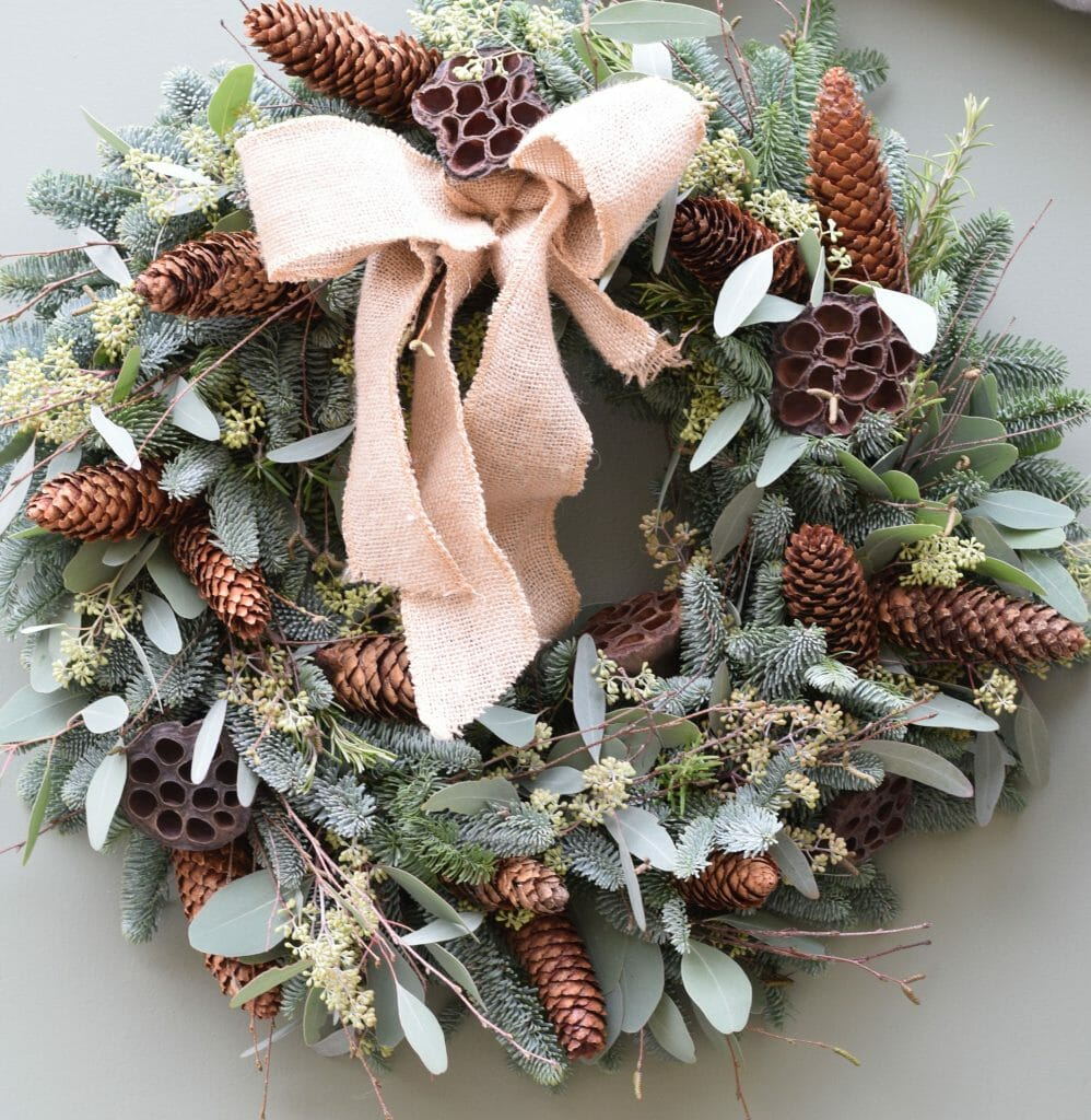 Christmas door wreath of mixed foliages and cones lotus heads available to order from Kensington flowers London