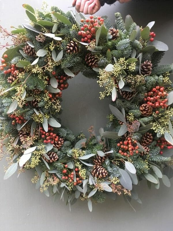 Photo showing a sample of a Mixed pine and foliage wreath with cones Kensington flowers London