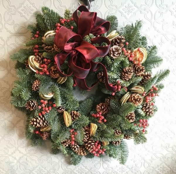 Photo showing a sample of a Pine, fruit, rosehip and cone Christmas door wreath Kensington Flowers London