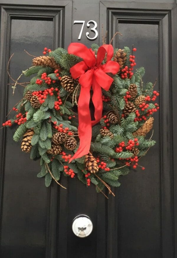 Photo showing a sample of a Pine ilex and cone door wreath Kensington Flowers London
