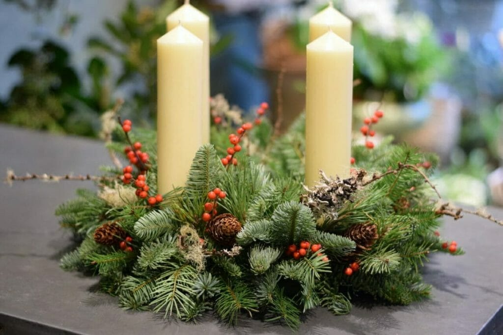 Photo showing a sample of a Christmas Advent candle arrangement mixed rustic foliages, lichen, berry and cones Kensington Flowers London